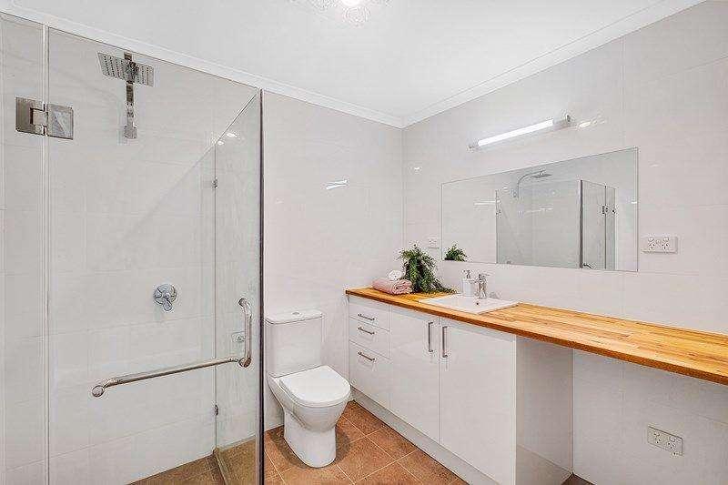 Nhà tắm với vòi hoa sen và tủ kệ đầy đủ